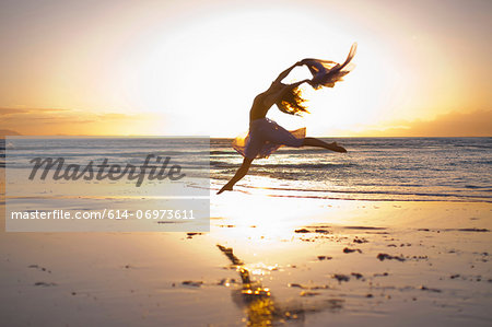 Young woman dancing on sunlit beach Stock Photo - Premium Royalty-Free, Image code: 614-06973611