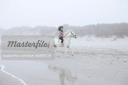 Woman riding horse on beach Stock Photo - Premium Royalty-Free, Image code: 614-06973728