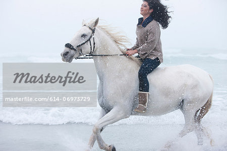 Woman riding horse on beach Stock Photo - Premium Royalty-Free, Image code: 614-06973729
