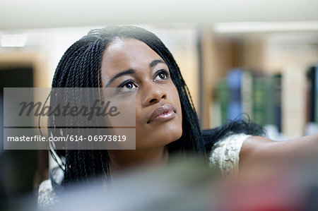 Female student choosing book in library Stock Photo - Premium Royalty-Free, Image code: 614-06973819
