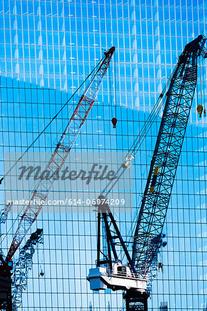 Construction cranes in front of office building Stock Photo - Premium Royalty-Free, Image code: 614-06974209