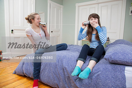 Girls sitting on bed playing with tincan telephone Stock Photo - Premium Royalty-Free, Image code: 614-06974393