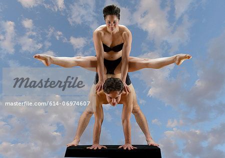 Mid adult dancers balancing on top of each other against blue sky Stock Photo - Premium Royalty-Free, Image code: 614-06974607