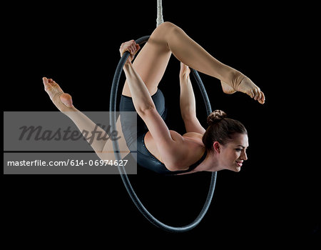 Aerialist performing on hoop in front of black background Stock Photo - Premium Royalty-Free, Image code: 614-06974627
