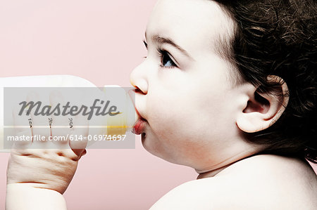 Portrait of baby girl drinking milk from bottle Stock Photo - Premium Royalty-Free, Image code: 614-06974697