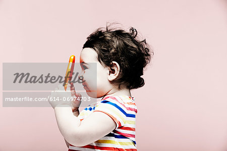 Portrait of baby girl holding plastic toy