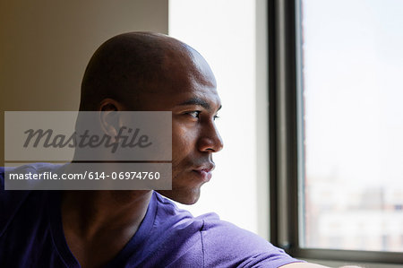Close up portrait of mid adult male looking out of window Stock Photo - Premium Royalty-Free, Image code: 614-06974760