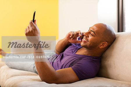 Mid adult male on sofa using digital tablet and mobile phone Stock Photo - Premium Royalty-Free, Image code: 614-06974767