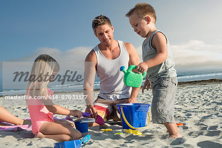 Young man playing with son and daughter on beach Stock Photo - Premium Royalty-Free, Image code: 614-07031177