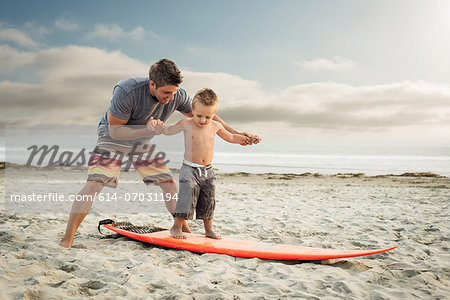 Young man teaching son to surf on beach Stock Photo - Premium Royalty-Free, Image code: 614-07031194