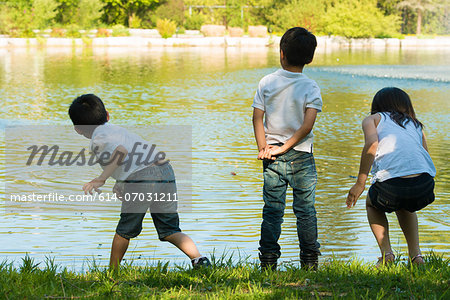 Three children playing by lake Stock Photo - Premium Royalty-Free, Image code: 614-07031211