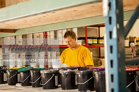 Man checking ink in screen print workshop Stock Photo - Premium Royalty-Free, Image code: 614-07031282