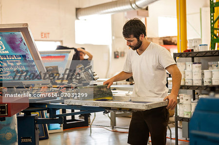 Worker pressing ink on frame in screen printing workshop Stock Photo - Premium Royalty-Free, Image code: 614-07031299