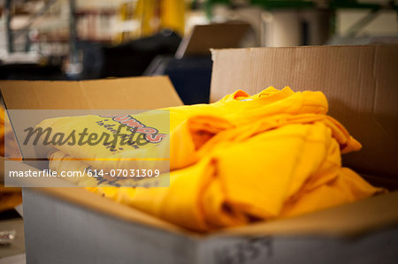 Open cardboard box containing screen printed t-shirts Stock Photo - Premium Royalty-Free, Image code: 614-07031309