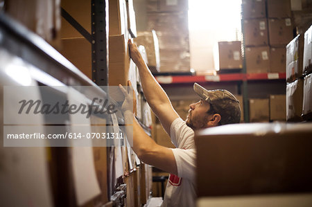 Worker reaching up for cardboard box stored in warehouse Stock Photo - Premium Royalty-Free, Image code: 614-07031311