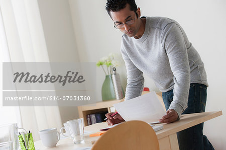 Male office worker reading paperwork Stock Photo - Premium Royalty-Free, Image code: 614-07031360