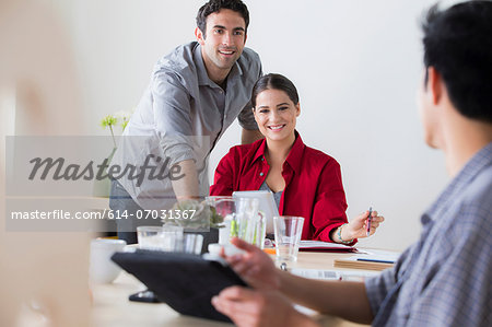 Office workers chatting at desk Stock Photo - Premium Royalty-Free, Image code: 614-07031367
