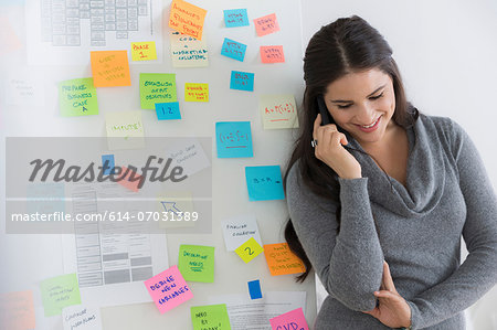 Portrait of female office worker using mobile Stock Photo - Premium Royalty-Free, Image code: 614-07031389