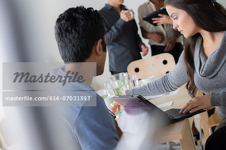 Office workers chatting around table Stock Photo - Premium Royalty-Free, Image code: 614-07031393