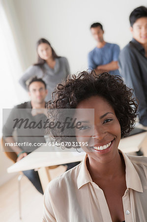Portrait of female office worker in front of colleagues Stock Photo - Premium Royalty-Free, Image code: 614-07031395
