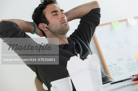 Portrait of male listening to earphones Stock Photo - Premium Royalty-Free, Image code: 614-07031401