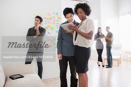 Office workers looking at digital tablet Stock Photo - Premium Royalty-Free, Image code: 614-07031408