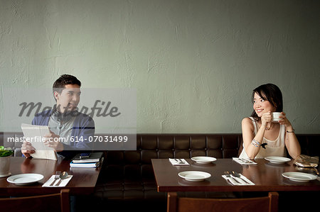 Young man and young woman smiling at each other in restaurant Stock Photo - Premium Royalty-Free, Image code: 614-07031499
