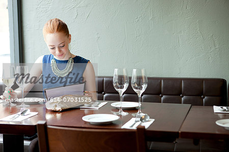 Young woman in restaurant, reading menu Stock Photo - Premium Royalty-Free, Image code: 614-07031525