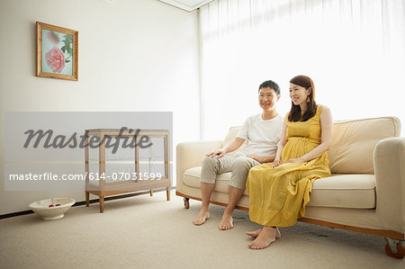 Man and pregnant woman sitting on sofa Stock Photo - Premium Royalty-Free, Image code: 614-07031599