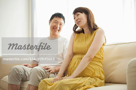 Man and pregnant woman sitting on sofa Stock Photo - Premium Royalty-Free, Image code: 614-07031603
