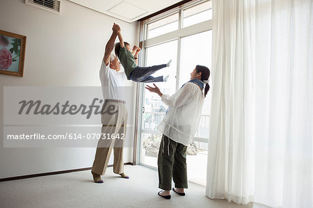 Grandfather and mother swinging young boy Stock Photo - Premium Royalty-Free, Image code: 614-07031642