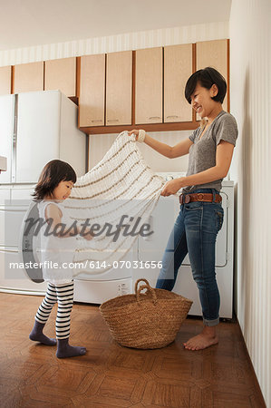 Mother and daughter folding towel Stock Photo - Premium Royalty-Free, Image code: 614-07031656