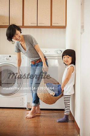 Mother and daughter with laundry basket Stock Photo - Premium Royalty-Free, Image code: 614-07031664