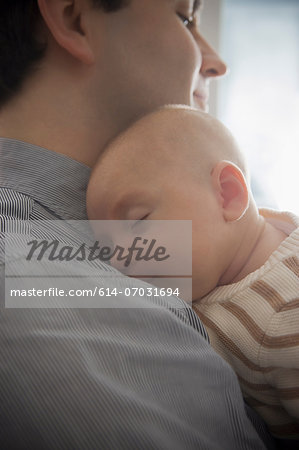 Baby boy sleeping on father's shoulder, close up Stock Photo - Premium Royalty-Free, Image code: 614-07031694