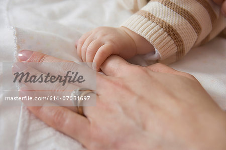 Baby boy holding mother's hand, close up Stock Photo - Premium Royalty-Free, Image code: 614-07031697