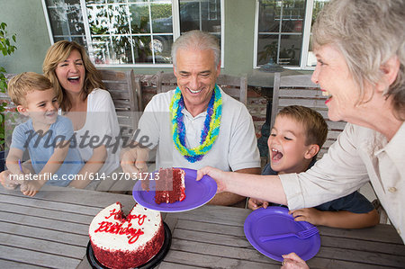 Senior woman serving slice of birthday cake at party with family Stock Photo - Premium Royalty-Free, Image code: 614-07031713