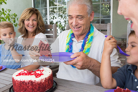 Senior man serving slice of birthday cake at party with family Stock Photo - Premium Royalty-Free, Image code: 614-07031714