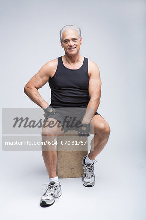 Senior man in sports clothing sitting in studio, portrait Stock Photo - Premium Royalty-Free, Image code: 614-07031757