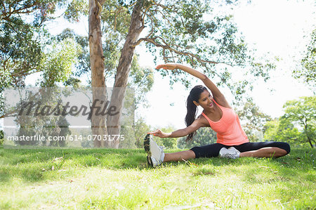 Young woman stretching in park Stock Photo - Premium Royalty-Free, Image code: 614-07031775