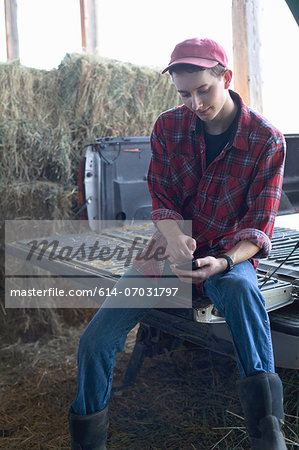 Young farmer sitting and using mobile phone Stock Photo - Premium Royalty-Free, Image code: 614-07031797