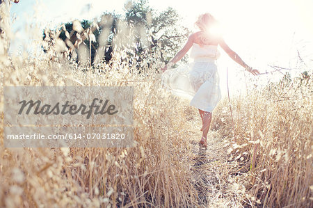 Woman walking through field touching grasses Stock Photo - Premium Royalty-Free, Image code: 614-07031820