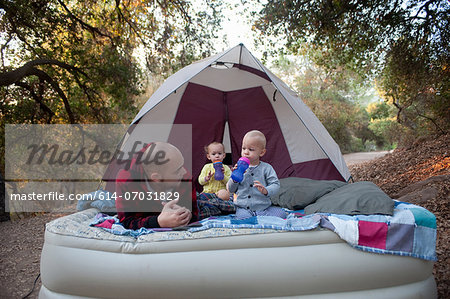 Toddler twins on camping mattress with father Stock Photo - Premium Royalty-Free, Image code: 614-07031829