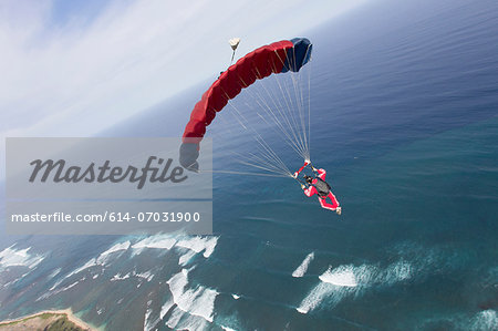 Skydiver with red parachute above Honolulu, Hawaii Stock Photo - Premium Royalty-Free, Image code: 614-07031900