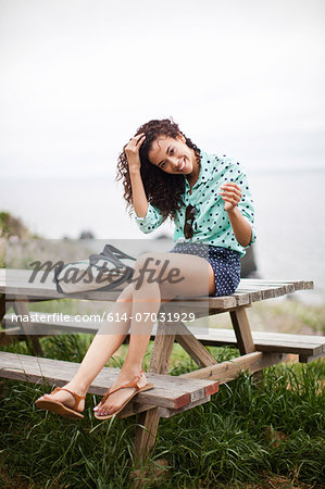 Young woman sitting on picnic table smiling, portrait Stock Photo - Premium Royalty-Free, Image code: 614-07031929