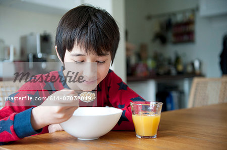 Boy eating breakfast cereal at table Stock Photo - Premium Royalty-Free, Image code: 614-07032019