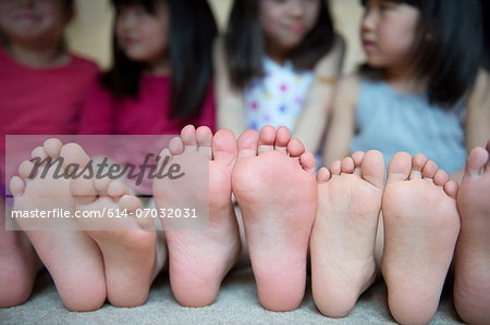 Girls sitting together with barefeet in a row Stock Photo - Premium Royalty-Free, Image code: 614-07032031