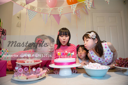 Girls blowing out birthday candles on cake Stock Photo - Premium Royalty-Free, Image code: 614-07032036