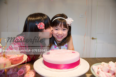 Girl kissing friend at birthday party Stock Photo - Premium Royalty-Free, Image code: 614-07032042