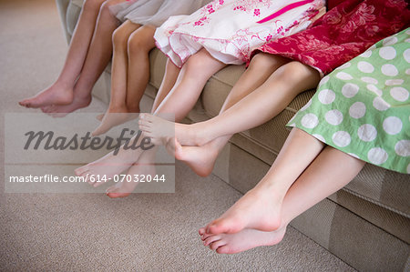 Girls sitting together in a row on sofa