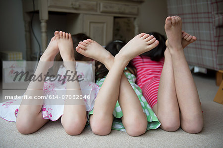 Girls lying on floor together with feet up Stock Photo - Premium Royalty-Free, Image code: 614-07032046